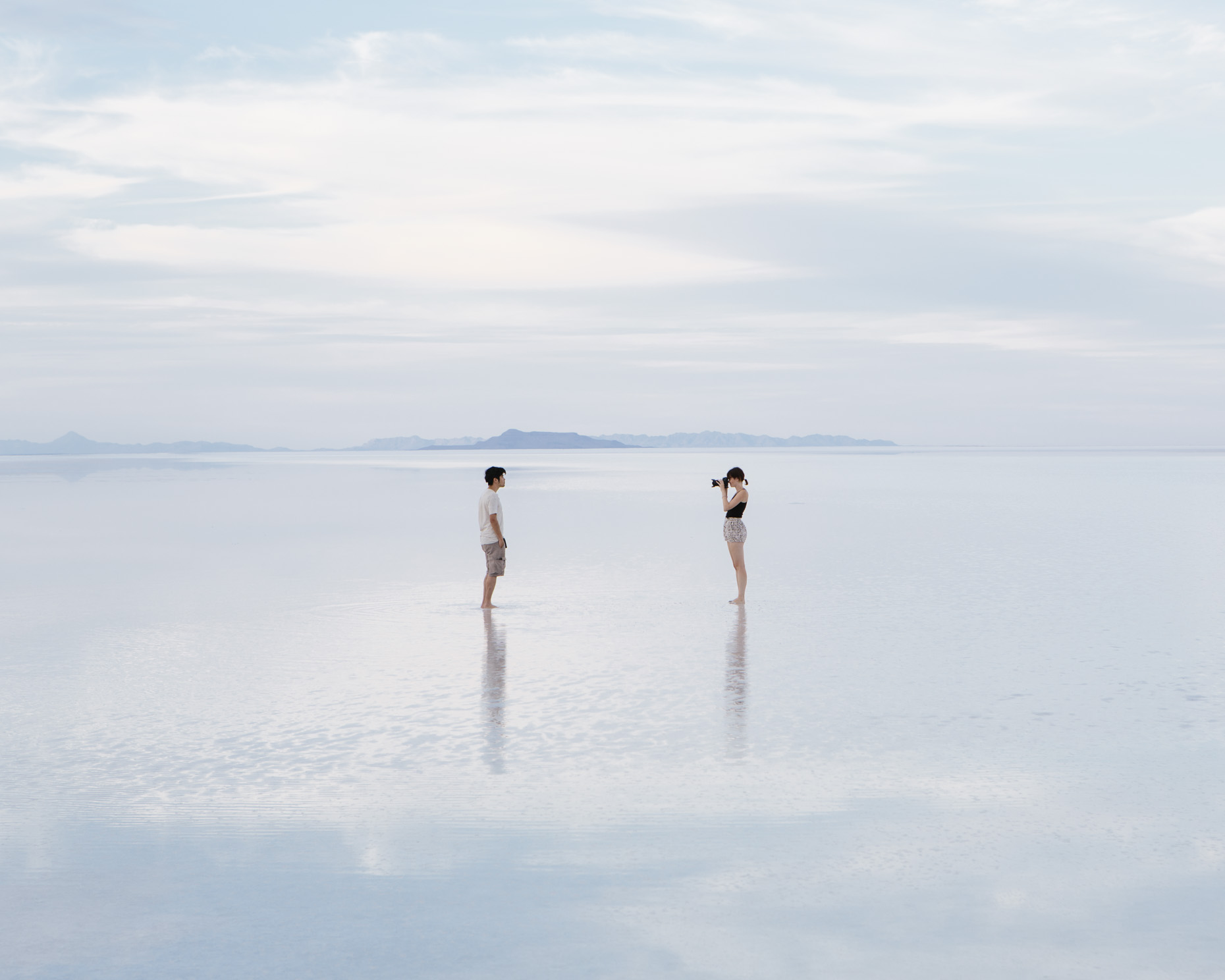 Couple taking photograph on flooded Bonneville Salt Flats, Utah - Paul Edmondson